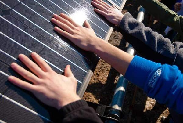 Hands touching solar panel